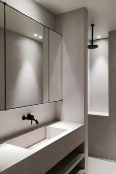 Micro cement wet room and sink with black, wall mounted taps and ceiling mounted shower head