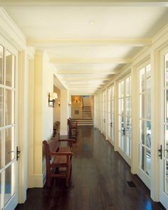 pale yellow entry hallway with wall of french doors, ivory, cream, french vanilla, dark wood floors, white trim, Sherwin Williams neutral ground used in interior design