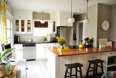 lovely kitchen- the post tells what the paint color is- nice and rich without being too dark- sets off the white cabinets nicely- also love the yellow drapes with those colors