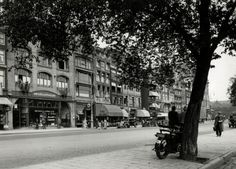 Motorfiets bij boom op Damrak in Amsterdam, vóór 1945.