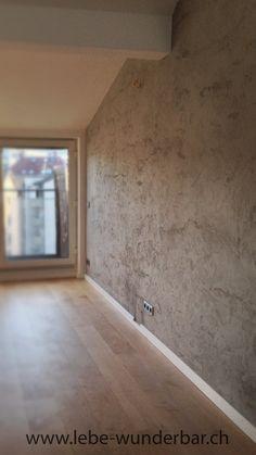 Wanddesign in Handarbeit mit natürlichem Kalkputz im wilden Travertinstyle. Dank natürlichem Kalk sind hochwertige Wandgestaltungen im Wohnzimmer und nachhaltiges Wohnen keine Gegensätze. Diese farbige Wand mit grauer Steinoptik und natürlicher Struktur unterstützt ein gutes Raumklima - nicht nur für Allergiker. Wunderbare Gestaltung aus Zürich.