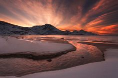Golden Sunset Wall Mural: Nature: Beach: A breathtaking scene of amber sun rays peer from behind snow-draped mountains. A river flows gently along the Norwegian snow banks and joins with the awaiting sea. A minimalistic wall mural image that can be printed on demand. Your specifications will be met for any interior design or home decor project. Create your own wallpapers, wall art and more by exploring our extensive collections.