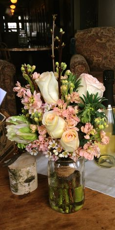 A bridal bouquet featuring roses, euphorbia, flowering plum, stock, and wax myrtle