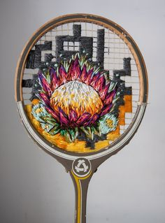 Cape Town-based designer and embroidery artist Danielle Clough uses thick, bright thread to create stunning images of flowers, portraits of people, and other images including fast food, emojis, and birds. Some of her most unusual pieces are different flowers hung on the strings of vintage badmin