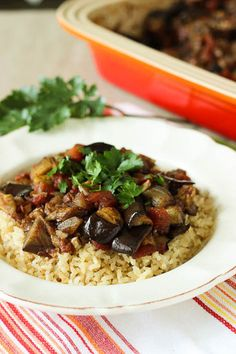 Lebanese Moussaka on top of brown rice, garnished with parsley