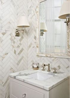Calacatta marble tile is a particular weakness of mine and I can't think of anything as classic or classy than herringbone-pattern subways from ArtisticTile in this powder room.