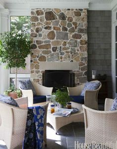 A huge fieldstone fireplace makes the screened porch an inviting outdoor room even on the coldest days. Design: Ann Wolf. housebeautiful.com