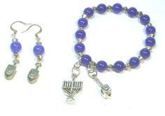 Hanukkah charms - the menorah and a dreidel dangle from a blue and silver stretch bracelet. @lindab142