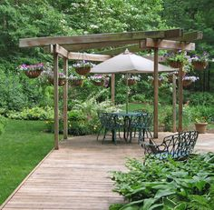 This uniquely shaped floating deck is large enough to support multiple focal points, from the dining area beneath a gazebo structure to the garden-backed bench seat area.