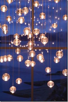 I bet I could make these using the CB2 glass ball idea since I know how to wire a pendant lamp- many little lamps on one circuit. Or battery operated mini LED lights in each? Hrm... I am so doing this!