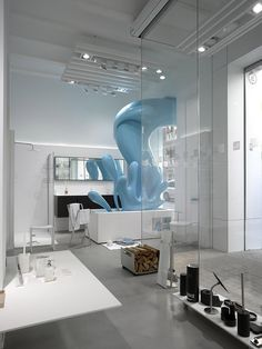 Hernandez Architects | Whimsical water splash sculpture from in front of store to inside that sells bathroom fixtures in Valencia, Spain