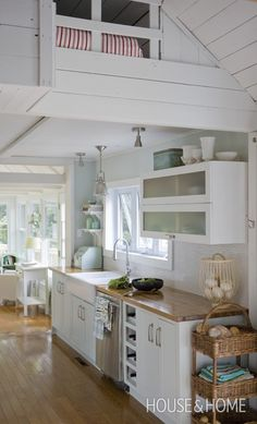 Visually expand a space with white. The narrow kitchen of this Laurentians, Que. cottage seems wider because of the white cupboards, simpl...