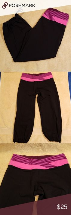 Lululemon Black Workout Capris in a Size 6 Adorable black workout capris from Lululemon in a size 6.  These capris have a pink and purple colored waist and drawstring around the cuff to loosen or tighten for comfort.  87% nylon, 13% lycra spandex.  These workout  capris measure 13 inches across the waistband and have a 21 inch inseam.   The cuffs measure 5 inches across, but can be tightened. There is a zippered pocket in back. Very gently worn and in great condition. lululemon athletica…