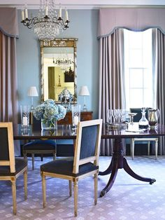 Traditional Dining Room with dark wood table, lavender rug, crystal chandelier, lavender draperies with valences.