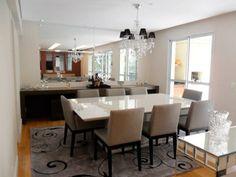 O espelho que toma toda a parede dá sensação de amplitude à sala de jantar assinada por Luiza Altman.