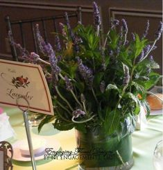 herbs wedding centerpieces pictures | Lavender pots wrapped in purple paper in clear bowls