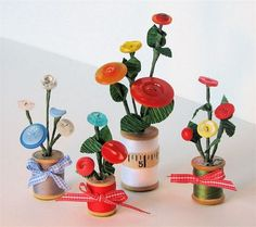 Button Flowers in Thread Spool Vases. They are decorated with bits of ribbon or vintage sewing supplies.