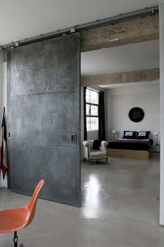 Industrial sliding door can be crated with wood panel, wheels, and simple track on ceiling... also platform bed