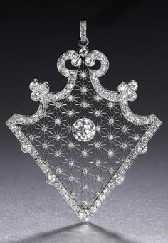 A Belle Epoque diamond brooch/pendant, circa 1910. The articulated triangular openwork plaque, centrally-set with a collet-set old brilliant-cut diamond, within star-shaped latticework accented by single-cut diamonds, to a scrolled border millegrain-set throughout with cushion-shaped and old brilliant-cut diamonds, detachable brooch frame. #BelleÉpoque #brooch #pendant