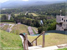 No snow? No problem at the Lake Placid Olympic Ski Jumping Complex in Lake Placid, New York where Olympic hopefuls can train year-round. Lake Placid Olympics, Rv Campgrounds, Ski Jumping, Winter Olympics, Garden Bridge, Day Trips, Skiing, Outdoor Structures, Snow