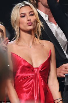 Pucker up: Showing off her eye-popping cleavage in the garment, which featured a plunging ...
