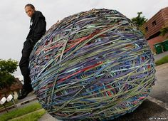 Joel Waul, 27, poses for a photograph with the rubber band ball that he created in the driveway of his home August 14, 2008 in Lauderhill, Florida