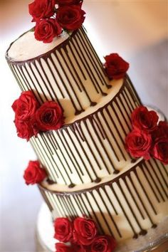 3-tier Wicked chocolate wedding cake iced in white chocolate ganache with dark chocolate drizzle, decorated with fresh red roses