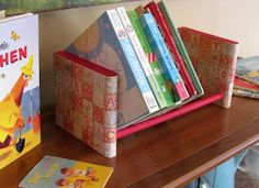 "Book shelf! You need:  • 2 (5 x 5 1/2"" x 3/4"") wood squares  • 3 dowels, I used 11"" x 1/2""   • 1/2"" drill bit OR the size to match your dowels  • FolkArt acrylic paint - Engine Red  • Scrapbook paper - two sheets  • Mod Podge  • Craft knife  • Wood glue"