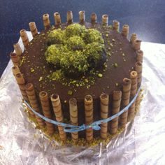 Nutella buttercream cake with pirouline rolled wafers. 3 layer cake -vanilla, chocolate, vanilla. Topped with cake balls covered in pistachio. :)