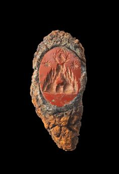 Fragment of an iron ring with a gemstone made of red cornelian showing the Mount Argaios with enthroning eagle in wreath and two stars. Roman, 2nd - 3rd century A.D. Gemstone intact, fragment corroded.