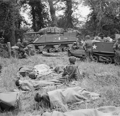 A Royal Artillery command post, probably from a 105mm SP M7 Priest Field Regiment, near Hermanville-sur-Mer, 6th June. The Sherman OP (observation post) tank in the background has a small 'GD' tactical marking on the side of its hull, indicating the GPO (Gun Position Officer) of B Troop, 2nd Battery. Motorcycle despatch riders and a Universal Carrier can also be seen. Some troops are bedding down in the foreground.