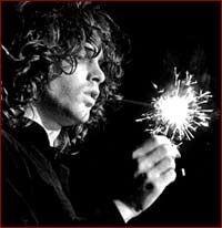 Jim Morrison with a sparkler on stage.
