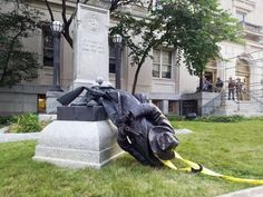 A protester climbed a ladder to place a rope around a Confederate statue at the Durham County Courthouse during an 'Emergency Durham Protest' in response to the violent protests Saturday in Charlottesville, on Monday, Aug. 14, 2017, in Durham, North Carolina. The group pulled down the soldier statue and proceeded to march to the site of the new police headquarters under construction.