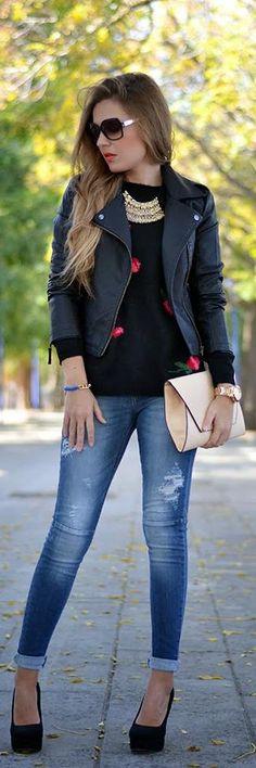 Jeans, black pumps, black leather jacket, graphic sweater, beige clutch ☑️