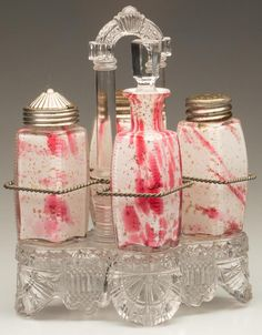 ZIPPERED CORNERS / ROYAL SILVER (OMN) FOUR-BOTTLE CASTER SET, cased opal with cranberry spatter and gold mica flakes, comprising a salt and pepper shaker with matching period lids, a cruet with stopper, and mustard pot with a period lid. Fitted in an appropriate glass stand. Attributed to Northwood Glass Co. Fourth quarter 19th century.