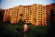 """GEORGIA. Abkhazia. Sukhum. 2005. Babushka """"Tanya,"""" an elderly ethnic Russian woman, heads back to her bombed out apartment building after walking her dog. Despite the damages, three apartments remain occupied in the building."""