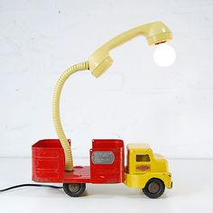 Some clever cloggs rigged up a light kit to this toy truck and old school phone , morphing it into a table lamp.
