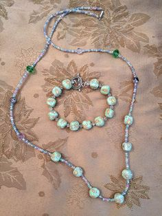 Long necklace and bracelet made with pastel seed beads, faceted glass and green floral fimo beads.