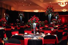 black tie event with tall red rose centerpieces. Black and red linens.
