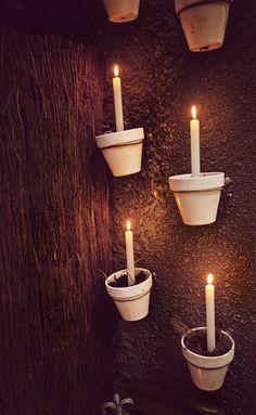 Garten Beleuchtung Idee - einzelne Tontöpfe mit einer Drahtschlaufe an der Wand befestigen und mit Erde und einer Kerze bestücken.