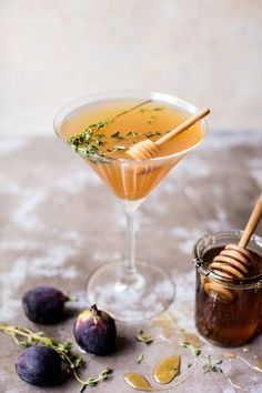 Honey and fig martini garnished with fresh thyme next to a glass honey jar and three fresh figs by {halfbakedharvest}