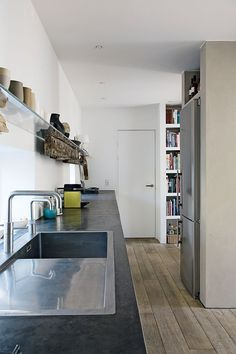 Raw kitchen with concrete counter top, rough wooden decor and a steel fridge built in the back of the chimney.