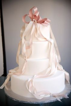 White frosting wedding cake with pink ombre bows