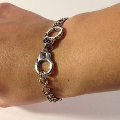 Mix into your arm candy some mob style with this handcuff bracelet!  Silver plated chain.  Clasps at the handcuff.