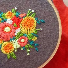 Neon dandelions - bright embroidery on a grey background.