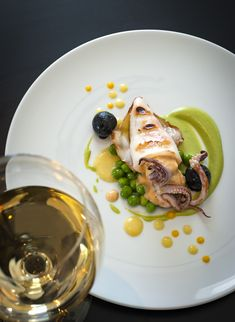 Grilled calamari stuffed with air dried salami foam, ink potatoes, spring peas, yellow tomato coulis at Grace Santorini.