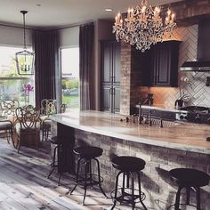 What an amazing kitchen. Love the wood floors, chandelier and big island.