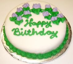 """Scotts Cakes Single Layer Decorated Cake Topped with Rolled Fondant 8"""" Rd. Red Velvet Cake with Blue Trim and Purple Flowers $19.95"""