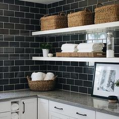 Long white floating shelves are fixed in a black and white laundry room to black subway backsplash tiles over white kitchen cabinets donning oil rubbed bronze pulls and a gray quartzite countertop. Farmhouse Kitchen Tables, Modern Farmhouse, Farmhouse Homes, Living Room Decor Fireplace, White Laundry Rooms, White Floating Shelves, White Shaker Cabinets, Quartzite Countertops, Laundry Room Cabinets