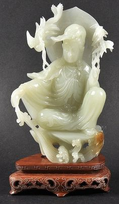 A GOOD EARLY 20TH CENTURY CHINESE CARVED GREEN JADE FIGURE OF GUANYIN modelled seated with an attached bird. Good condition. 6.5ins high.